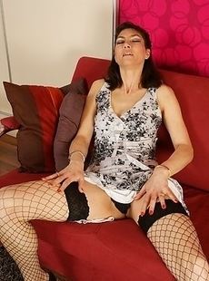 Hot MILF playing with her wet pussy on the couch
